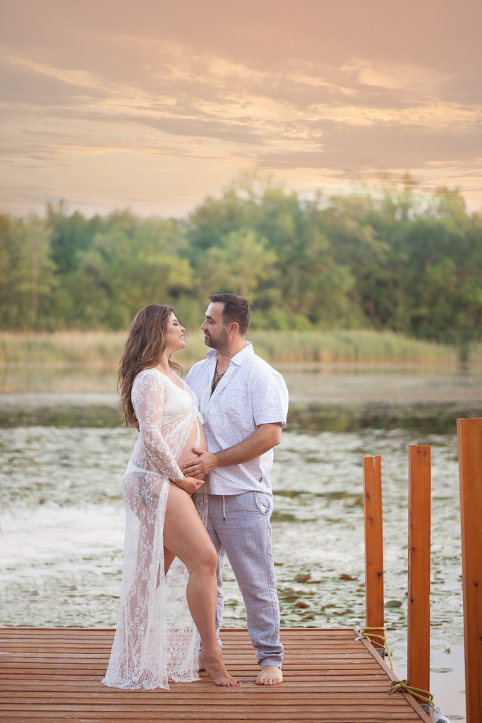 Gorgeous couple poses near lake during maternity session