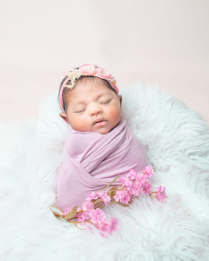 Stunningly Beautiful Newborn baby girl in a pink wrap with flowers